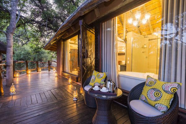 Lemon yellow cushions lift the taupe palette that blends in with the surrounding bushveld outside one of the aha Makalali River Lodge suites.